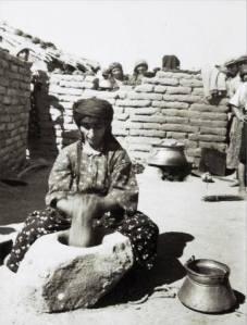Assyrische vluchteling - meer vluchtelingen op de achtergrond - die bulgur stampt in een pot in Tel Tamer in Syrië in 1939. Bulgur is een graanproduct gemaakt van verschillende soorten tarwe, maar meestal van durum (harde tarwe). (Foto: John David)