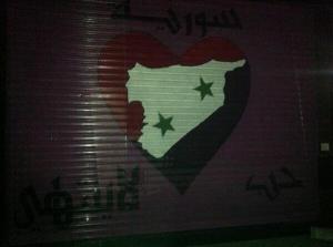 Een vitrinesluiting van een winkel met de Syrische nationale kleuren en de boodschap 'Eindeloze liefde voor Syrië'.