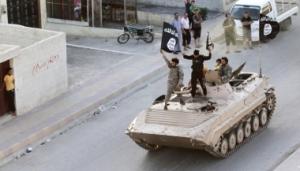 Militante Islamitische strijders houden de vlag van de Islamitische Staat (IS) omhoog tijdens een parade langs de straten van de noordelijke Ragga provincie in Juni 2014.  (Foto: Reuters)